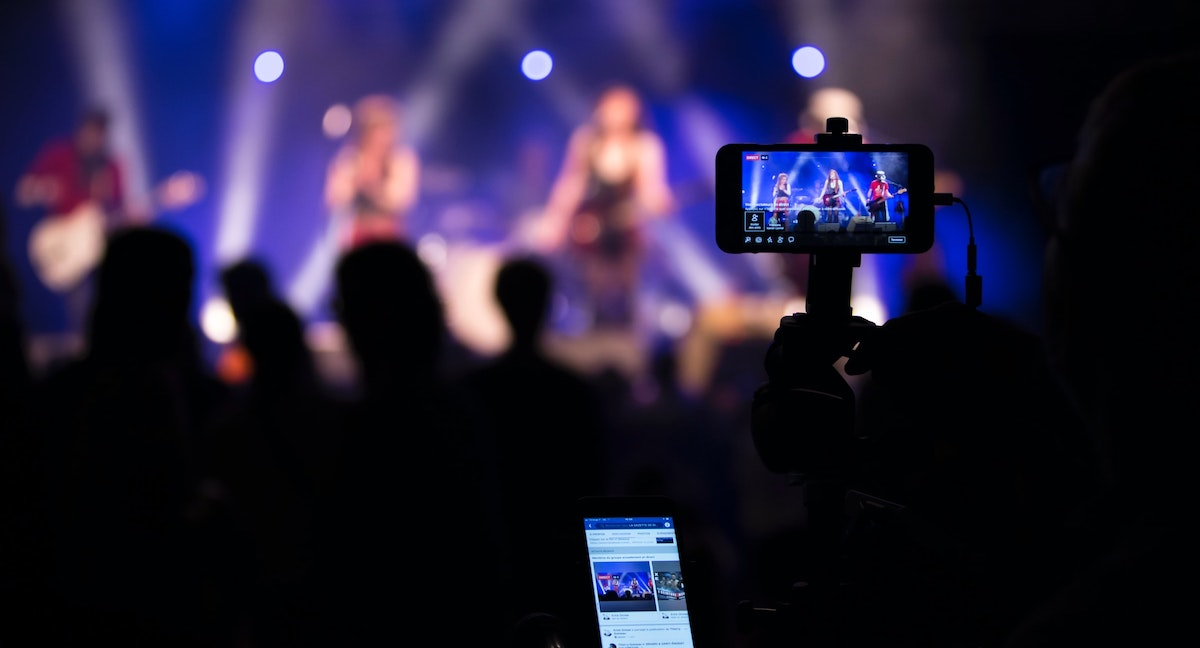 Photo of band performing in the background, with someone livestreaming the show from their phone in the crowd